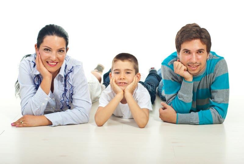 Famille heureuse s'asseyant sur l'étage dans une ligne photographie stock