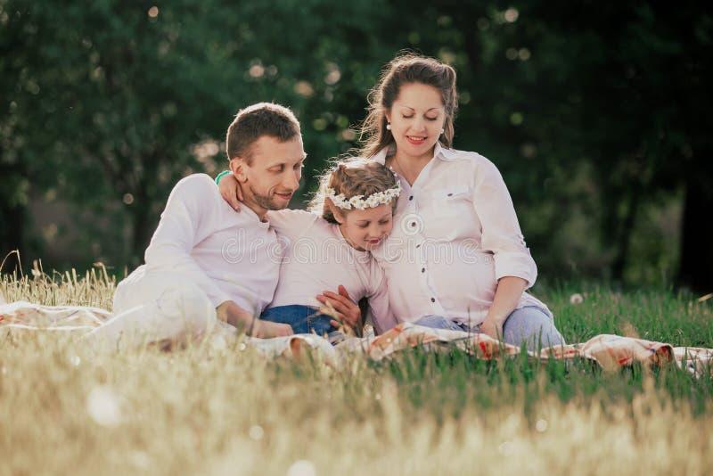 Famille heureuse s'asseyant sur l'herbe un jour d'?t? images stock