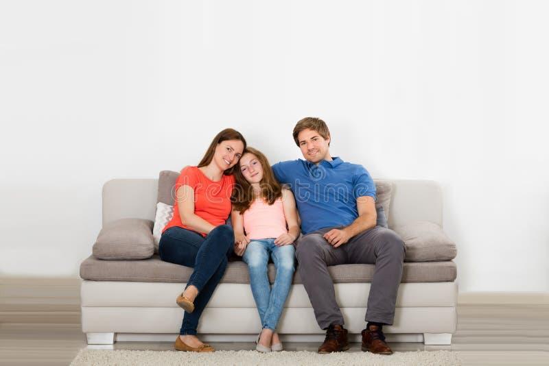 Famille heureuse s'asseyant sur le divan image stock