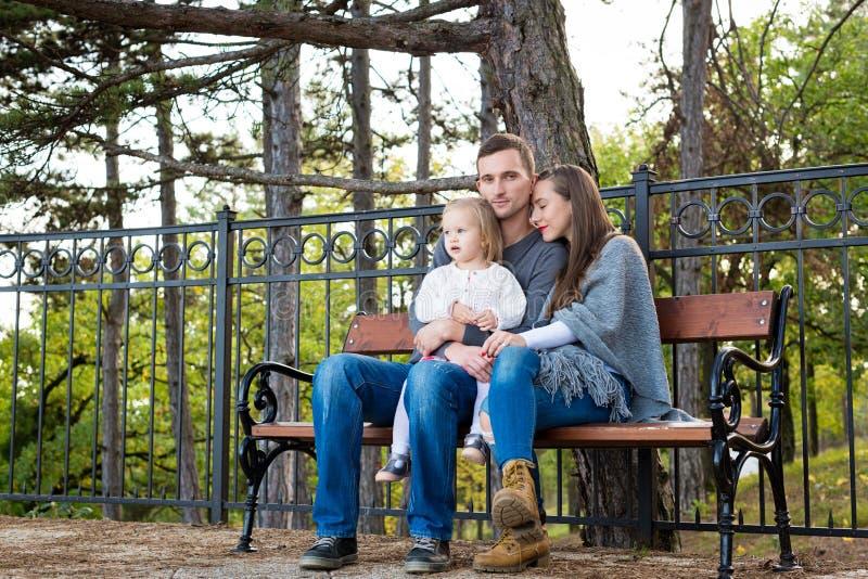Famille heureuse s'asseyant sur un banc en parc appréciant leur temps ensemble image libre de droits
