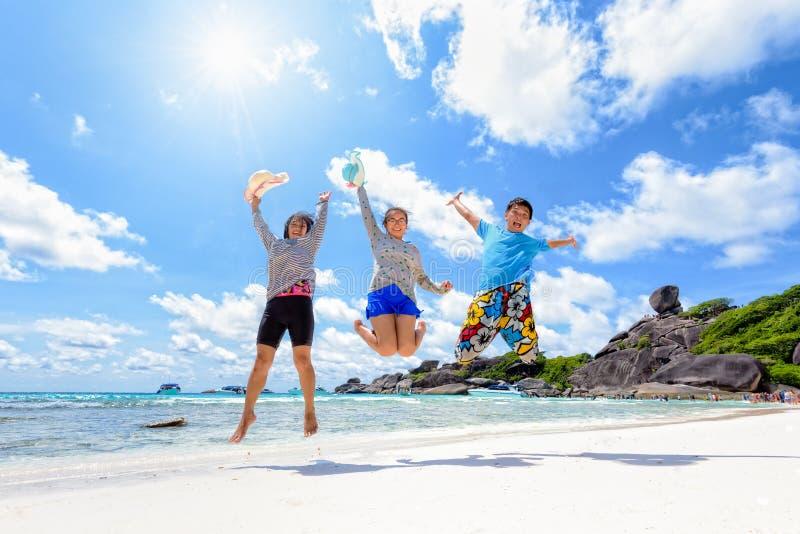 Famille heureuse sautant sur la plage en Thaïlande image stock