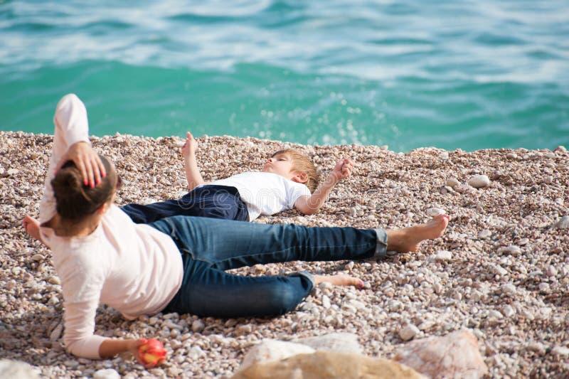 Famille heureuse se composant du mensonge de repos de mère et d'enfant sur la plage de mer dans le jour d'été images stock