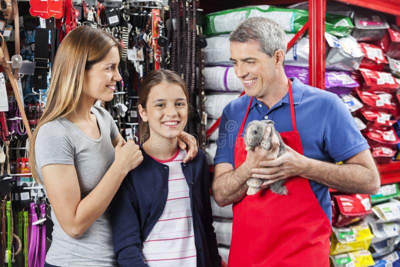Famille heureuse se tenant avec le magasin de Holding Rabbit At de vendeur photos stock