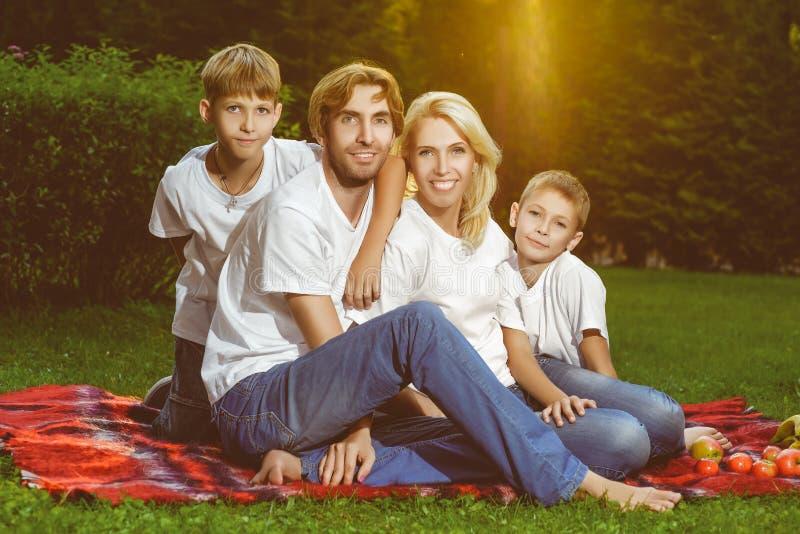 Famille heureuse se trouvant sur l'herbe en été Pique-nique photos stock