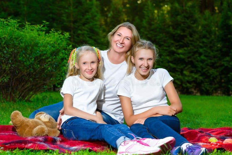 Famille heureuse se trouvant sur l'herbe en été Pique-nique photographie stock