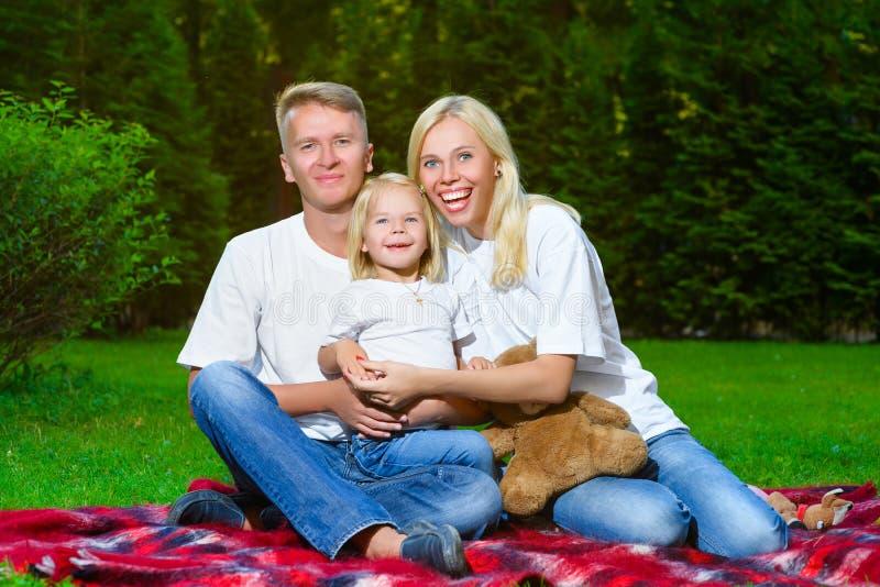 Famille heureuse se trouvant sur l'herbe en été Pique-nique image libre de droits