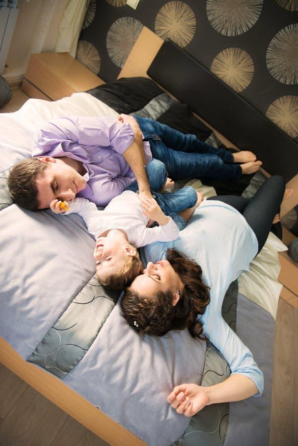 Famille heureuse se trouvant sur le lit images stock