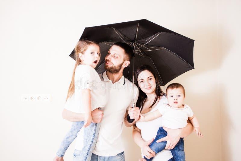 Famille heureuse sentant en sécurité sous le parapluie image libre de droits