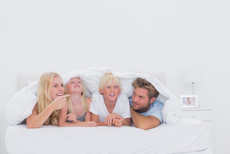 Famille heureuse sous la couette photo libre de droits