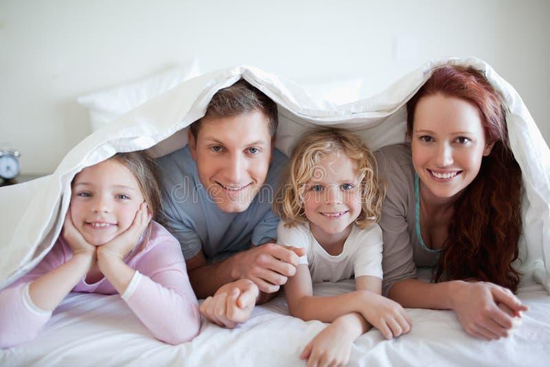 Famille heureuse sous le couvre-lit photos libres de droits