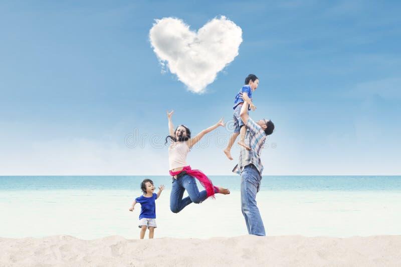 Famille heureuse sous le nuage de coeur à la plage photographie stock