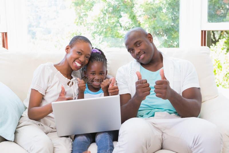 Download Famille Heureuse Sur Le Divan Avec L'ordinateur Portable Image stock - Image du couples, affection: 56485091