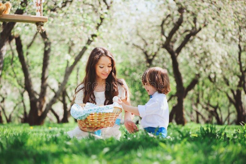 Famille heureuse sur le pique-nique pour le jour de mères Fils de maman et d'enfant en bas âge mangeant des bonbons extérieurs au images stock