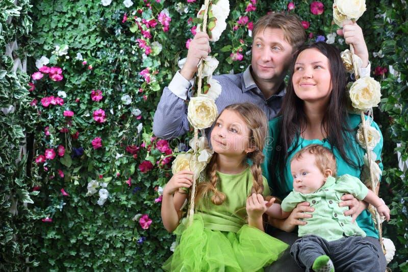 Famille heureuse sur le regard d'oscillation à la distance près de la haie photographie stock