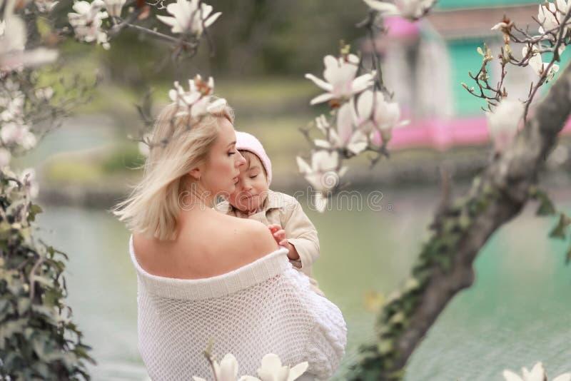 Famille heureuse sur un pré d'été fille de bébé d'enfant de petite fille étreignant et embrassant la mère photos libres de droits