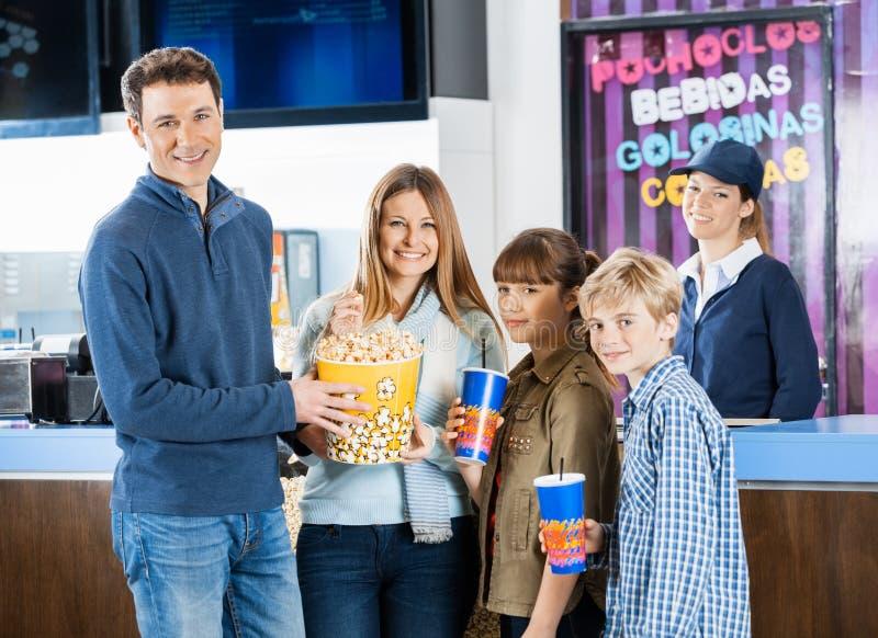 Famille heureuse tenant des casse-croûte à la concession de cinéma image libre de droits