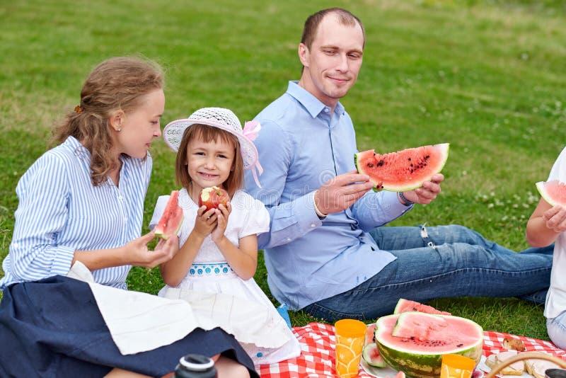 Famille heureuse ? un pique-nique mangeant la past?que M?re, p?re et enfant ? un pique-nique dans le pr? ou le parc photographie stock