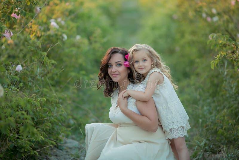 Famille heureuse : une jeune belle femme enceinte avec sa petite fille mignonne marchant dans le domaine orange de blé sur a image stock