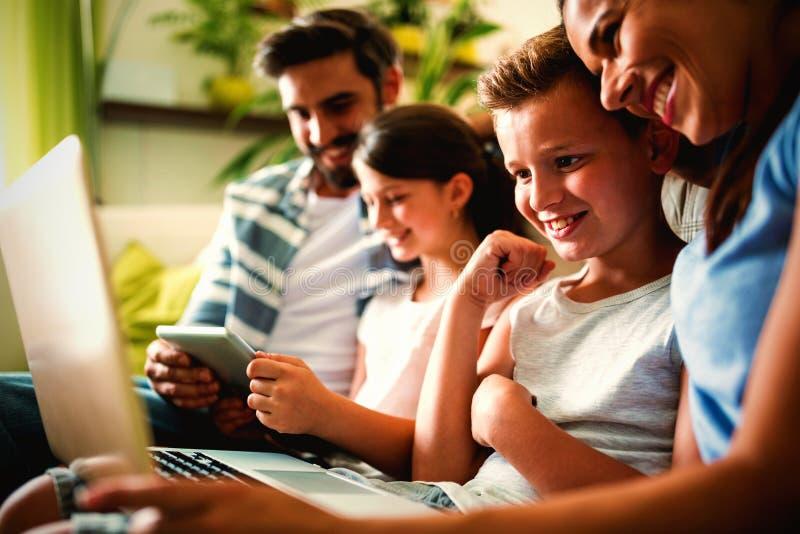 Famille heureuse utilisant l'ordinateur portable et le comprimé numérique dans le salon photographie stock libre de droits