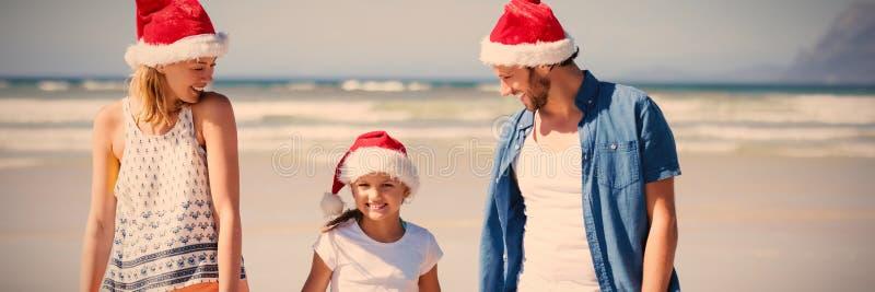 Famille heureuse utilisant le chapeau de Santa tout en se tenant à la plage photographie stock