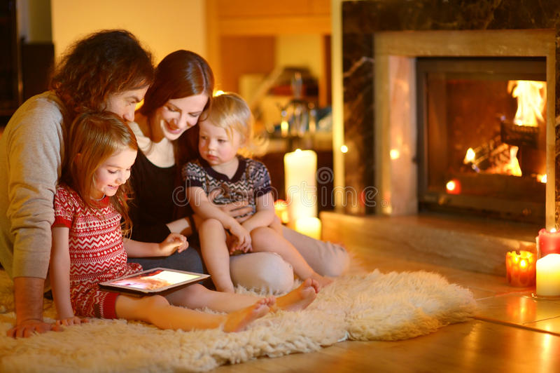 Famille heureuse utilisant un PC de comprimé par une cheminée photos stock