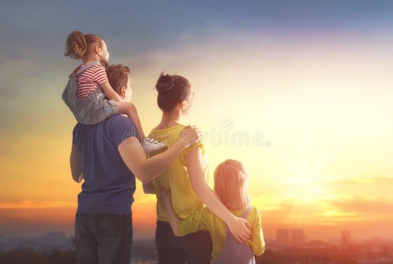 Famille heureux au coucher du soleil image stock
