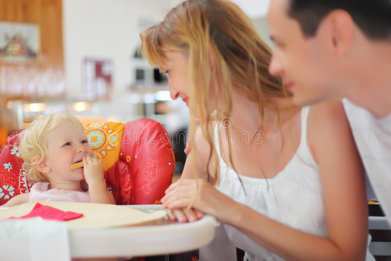 Famille heureux avec la petite fille blonde mangeant du pain image libre de droits
