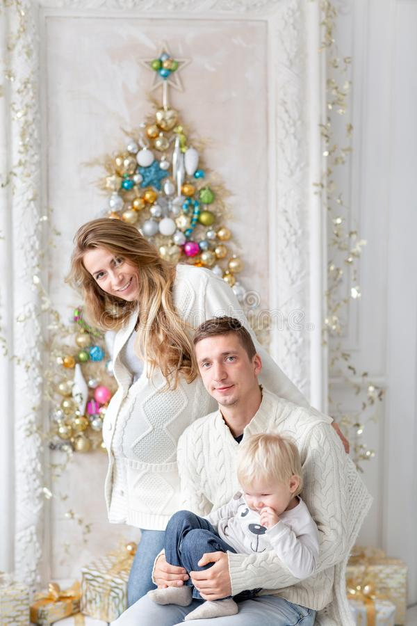 Famille heureux ayant l'amusement à la maison Matin de Noël dans le salon lumineux Jeunes parents avec le petit fils père photographie stock