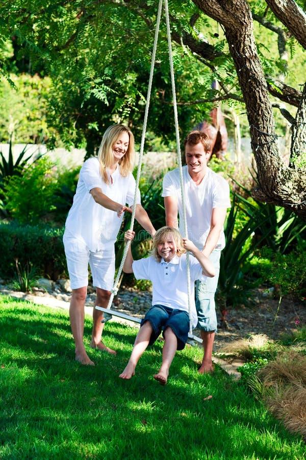 Famille heureux ayant l'oscillation d'amusement photos stock