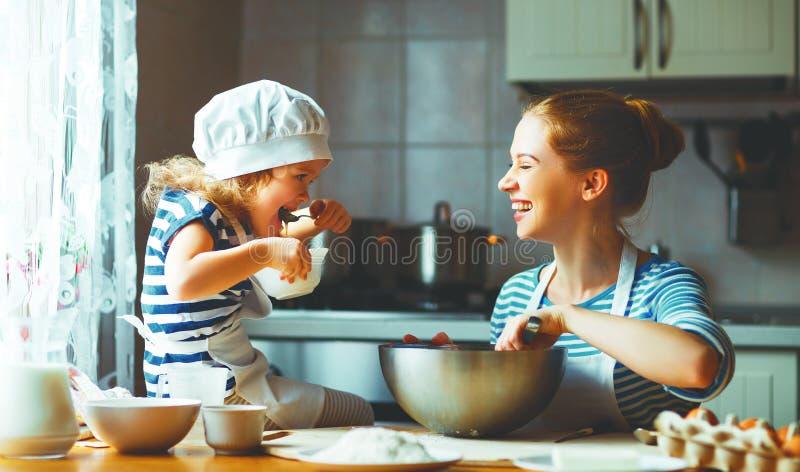 Famille heureux dans la cuisine la mère et l'enfant préparant la pâte, font cuire au four photo stock