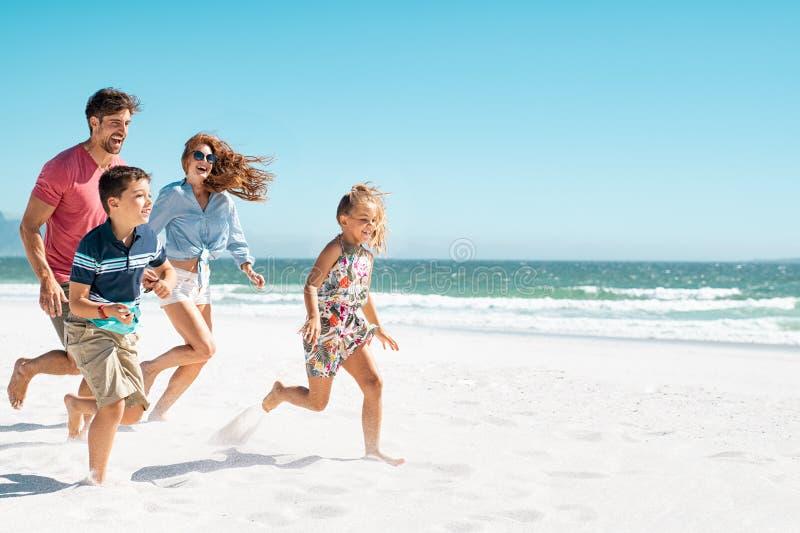 Famille heureux exécutant sur la plage photographie stock