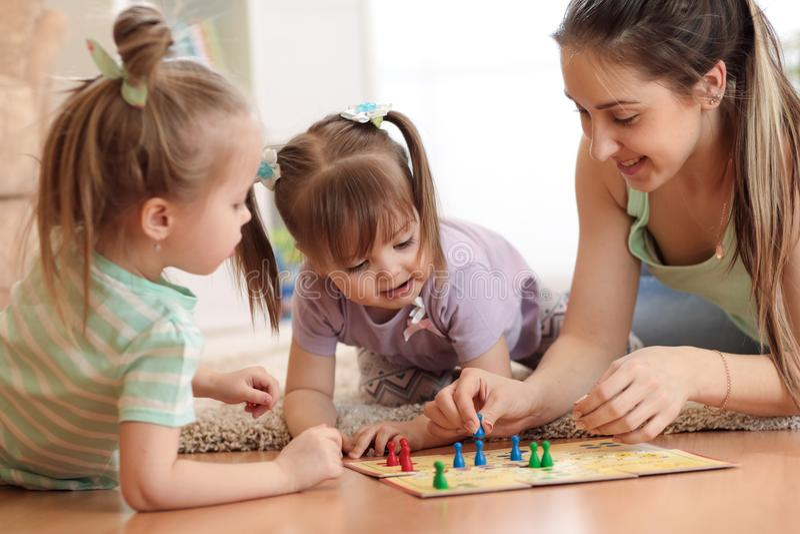 Famille heureux Jeune mère jouant le boardgame de Ludo avec ses filles tout en passant le temps ensemble à la maison image stock