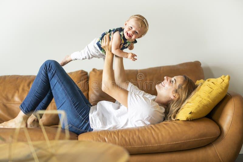 Famille heureux Jeux de fille de mère et de bébé, sur le sofa photos libres de droits