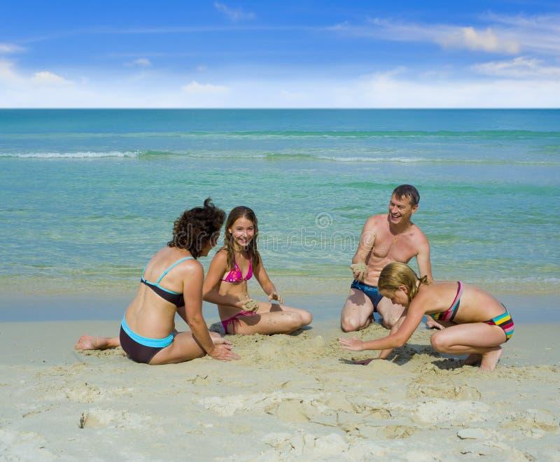 Famille heureux jouant à la plage photographie stock libre de droits