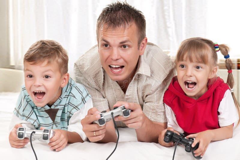 Famille heureux jouant un jeu vidéo images stock