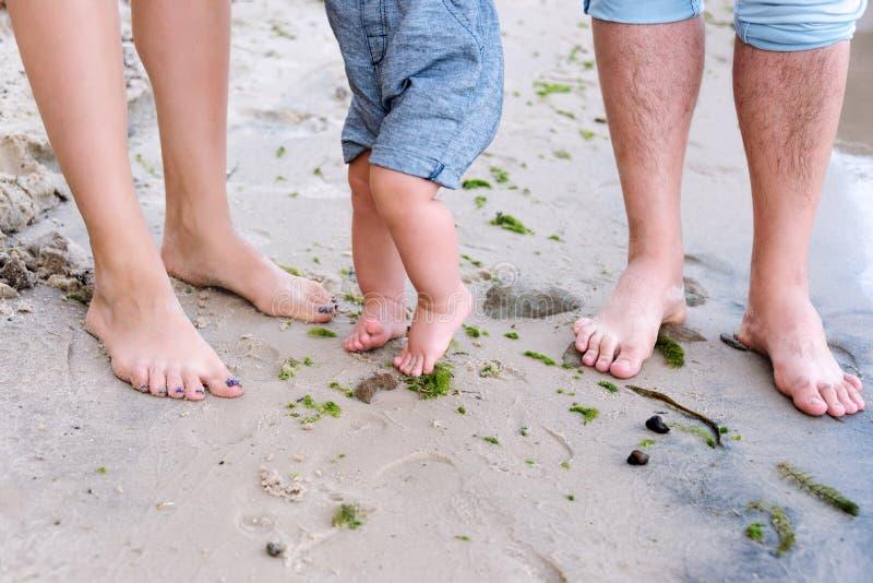 Famille heureux sur la plage Plan rapproché des pieds de la famille avec le petit bébé garçon marchant sur le sable Homme et femm photo stock