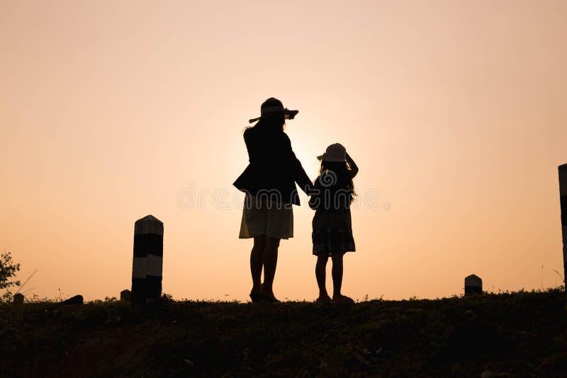 Famille heureux Une mère et un fils jouant dans des domaines d'herbe dehors à la silhouette de soirée Ton de vintage et espace de images libres de droits