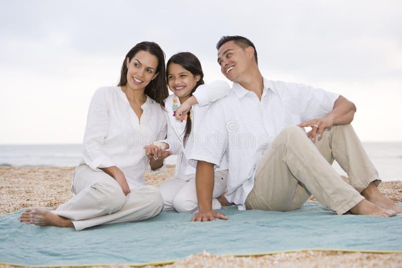 Famille hispanique avec la petite fille sur la couverture de plage photographie stock