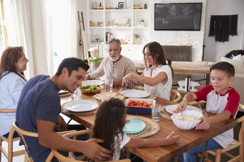 Famille hispanique de trois générations se reposant à la table avant dîner photos stock