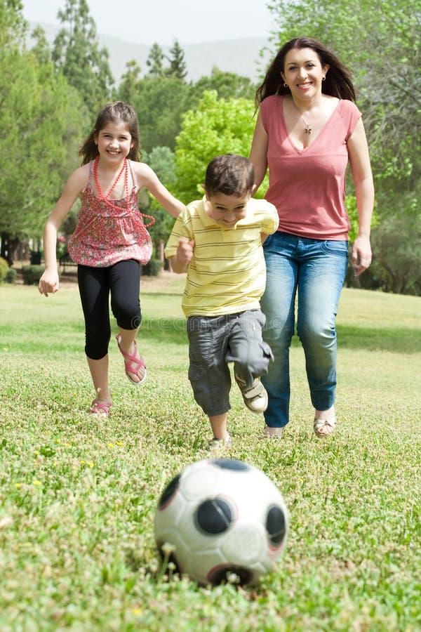 Famille jouant au football et ayant l'amusement image libre de droits