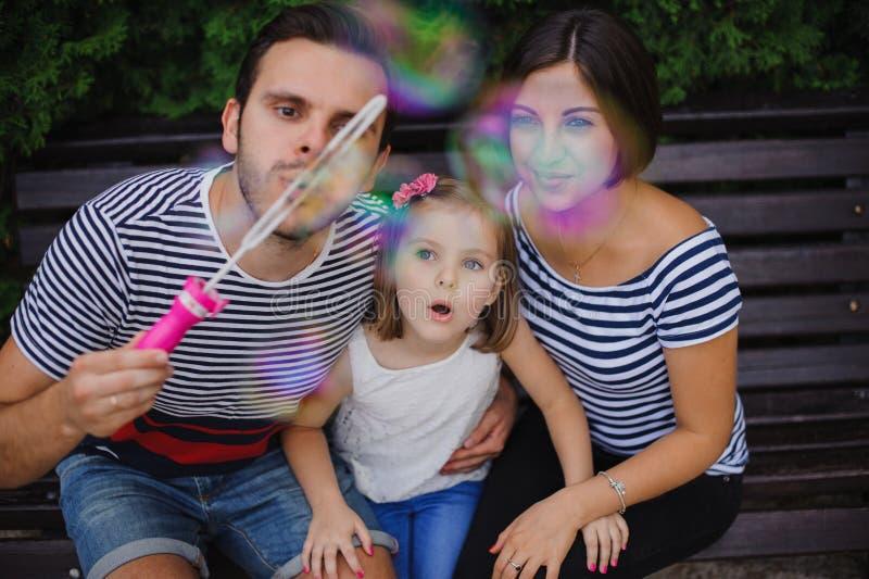 Famille jouant avec des bulles dans le jardin images stock