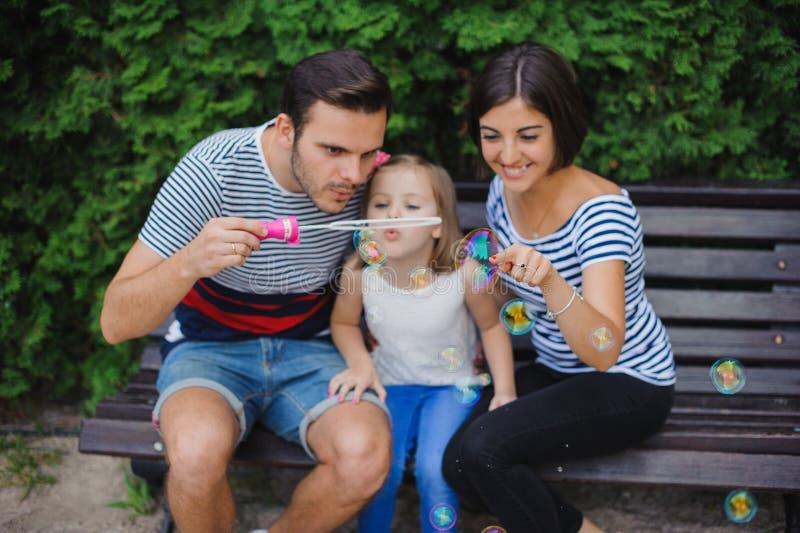Famille jouant avec des bulles dans le jardin photos stock
