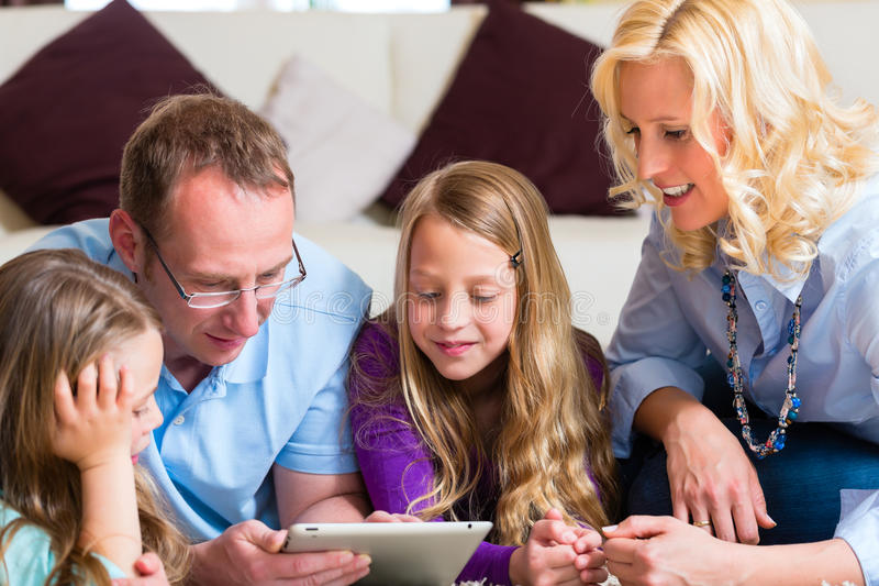 Famille Jouant Avec L Ordinateur De Tablette à La Maison Photos stock