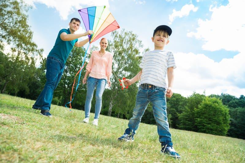 Famille jouant avec le cerf-volant images stock