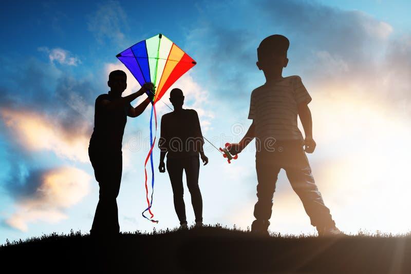 Famille jouant avec le cerf-volant color? photos stock