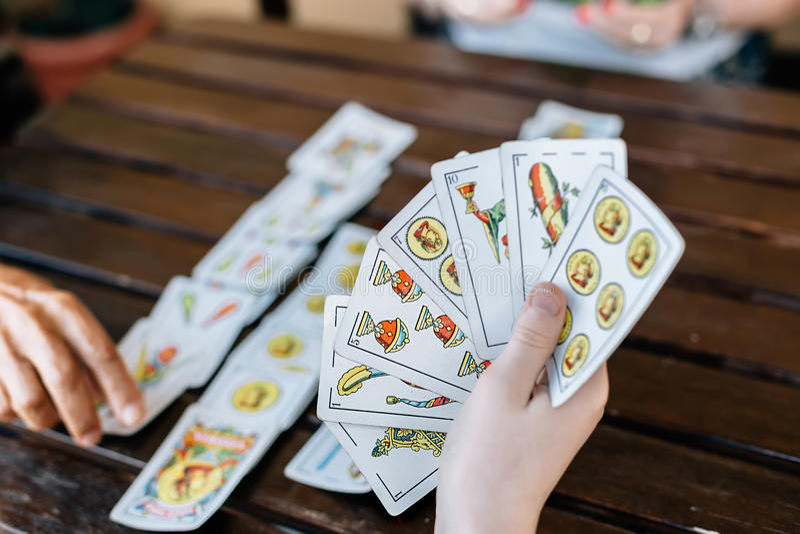 Famille jouant des cartes Fermez-vous vers le haut des mains image libre de droits