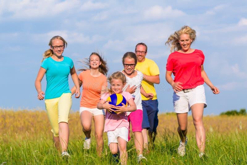 Famille jouant des jeux de boule sur le pré images stock