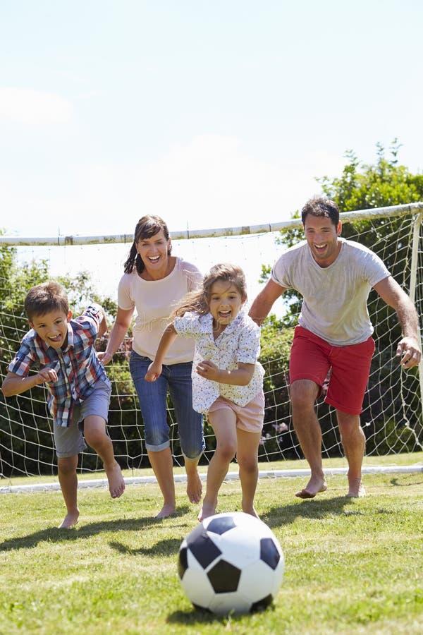 Famille jouant le football dans le jardin ensemble photo libre de droits
