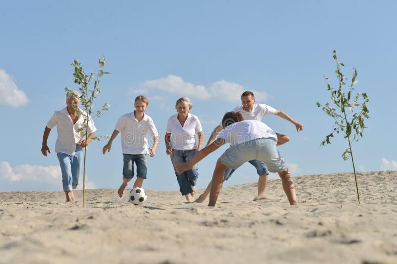 Famille jouant le football sur une plage dans le jour d'été photo stock