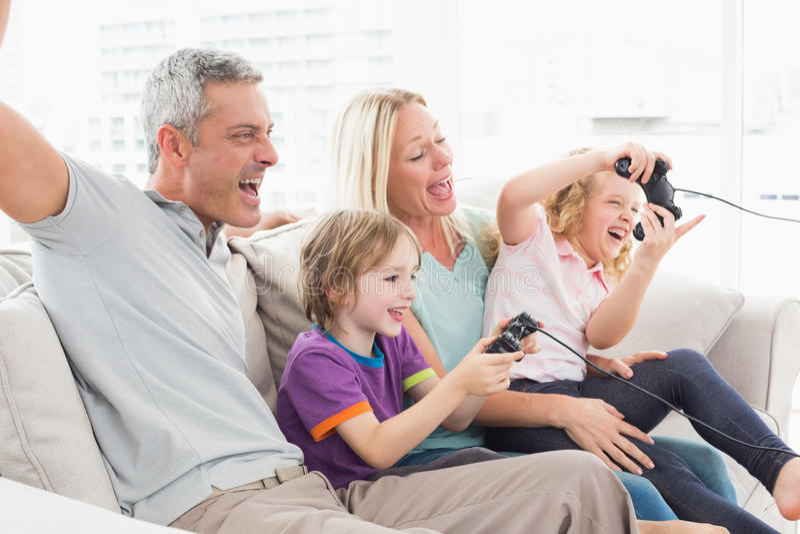 Famille jouant le jeu vidéo tout en se reposant sur le sofa images stock
